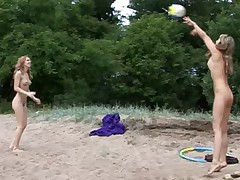 Two nude gymnasts play and exercise on the beach