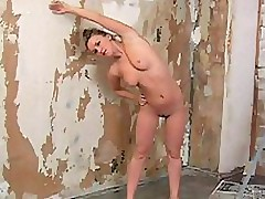 A curvy blonde performing nude workout in the trashy looking room