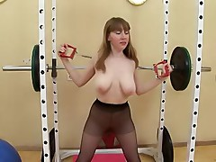 Black pantyhose gymnast stretches an expander