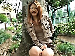 Pretty Japanese babe plays with her pussy while sitting outside