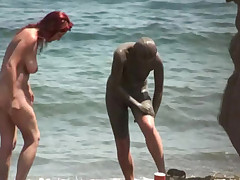 Nudist women cover themselves in sea dirt