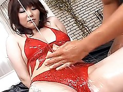 Japanese beauty in red is oiled up and looks very sexy when she is wet