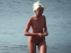 Cute naked blonde flirting on the beach