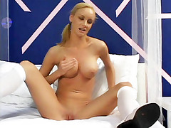 Busty blonde Leah Wilde cups her perky breasts while dipping a well lubricated dildo into her hole