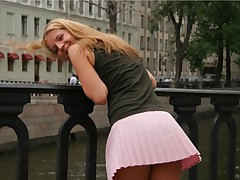 Lovely pink mini skirt wearing blonde poses outdoors in the park