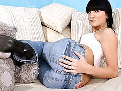 Slender brunette with gorgeous ass poses in her skin tight denim jeans