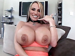 Busty vixen Lisa Lipps brandishes her enormous racks while sucking off a cock and gets cum glazed