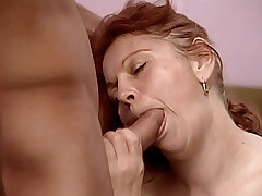 Mature redhead Stella sits in the corner of the bed sucking a huge cock like a lollipop