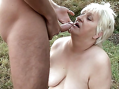 Mature hottie Anna Mary gets spoon fucked in the grass by a man wearing a mask